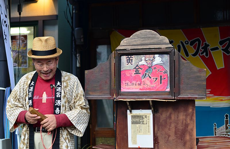 Figure 10: A contemporary kamishibai performer in Tokyo. Note the stage-like wooden box, into which paper panels are inserted. Photo by Aki Sato.