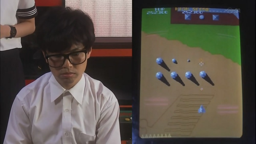 Figure 3: Screenshot from the first episode of the 2013 television series No kon kiddo: bokutachi no geemushi (No Continue Kid: Our Game History) broadcasted on TV Tokyo, a drama focusing on the history of Japanese arcades, and in which Xevious plays a central role. Taken by the author.
